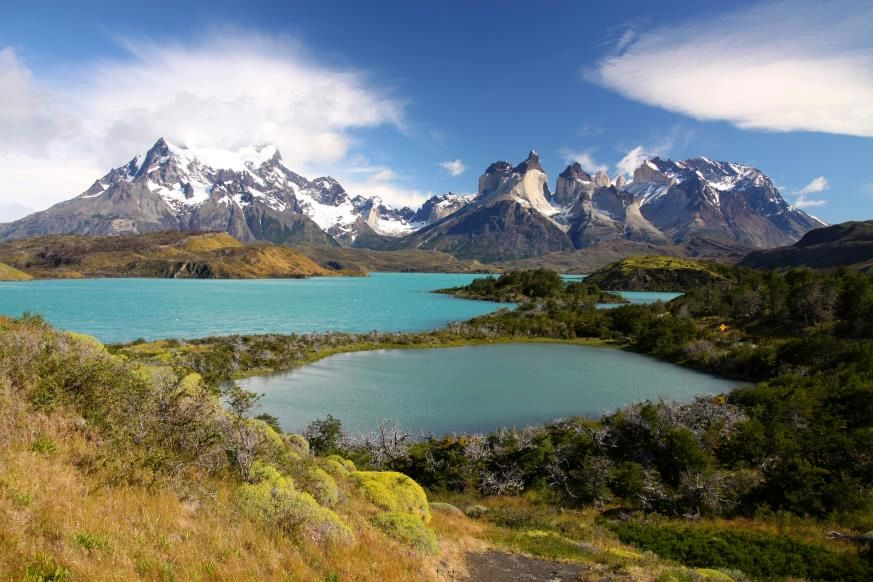 """Slide 15 of 16: This luminous lake in remote Patagonia, southern Chile, often reflects the spiky mountains called Cuernos (""""horns"""") del Paine that surround it in Torres del Paine National Park. Fed by glacial waters, the lake has brilliant colors of all shades that seem to change throughout the day as the light shift—besides hues of turquoise and blue, lavender, and even orange may appear. In addition to the water's shimmering beauty and the majestic peaks towering over it, the area around the lake is home to some of South America's most interesting wildlife, including the guanaco, a """"camelid"""" that resembles a llama or alpaca."""