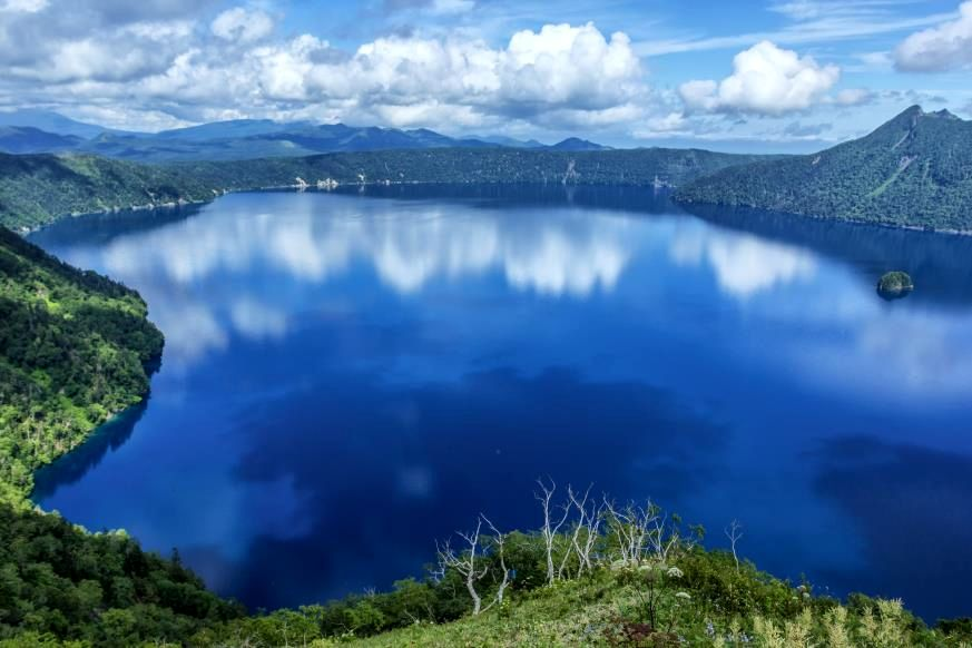 """Slide 10 of 16: Another caldera lake that formed from volcanic eruption thousands of years ago, this bedazzling body of water on Japan's island of Hokkaido is part of Akan-Mashu National Park. Called the """"lake of the gods,"""" it is often covered in fog and mist—to see the surface of the water is said to bring bad luck from the spirit who lives in its depths. But when it can be seen, the lake itself is crystal clear, with water visibility close to 100 feet, because no rivers empty into it to deposit sediment and debris. Nearby, Kaminoko-ike (""""child of the gods"""") Pond got its name because underground springs from Lake Mashu are believed to feed it, which is why the pond also has such transparent water. This is the real difference between a pond and a lake."""