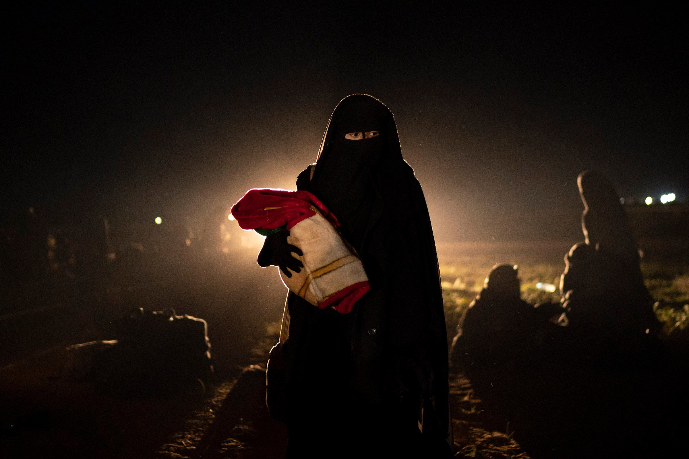In the Syrian desert outside Baghouz, a woman resumes her journey after being screened by the U.S.-backed Syrian Democratic Forces on Feb. 25. She and her infant were among hundreds of civilians in a series of mass evacuations from the last sliver of the country's territory still held by ISIS.