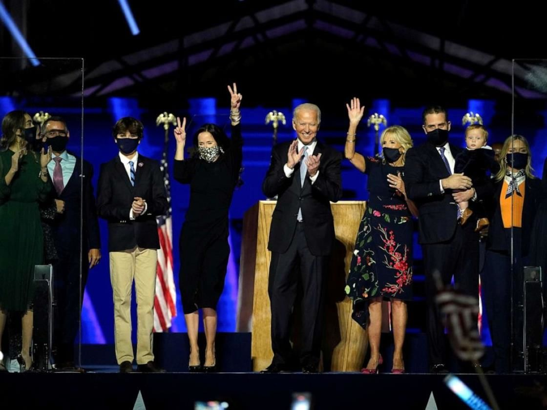 Joe Biden et al. standing on a stage posing for the camera: President-elect Joe Biden is accompanied on the stage by his wife Jill, and members of their family, after speaking in Wilmington, Del., Nov. 7, 2020.