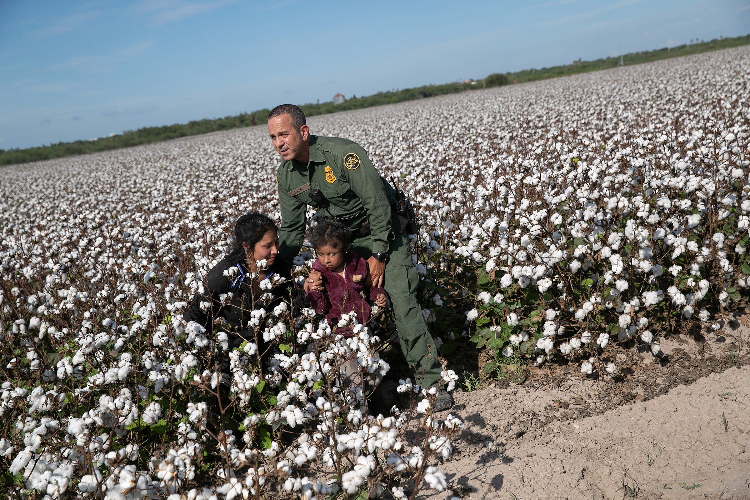 U.S. Border Patrol agent Carlos Ruiz apprehends a mother and daughter from Ecuador in Penitas, Texas, on Sept. 10. The undocumented immigrants had been hiding for hours in a cotton field after border agents detected and chased their group earlier in the day.