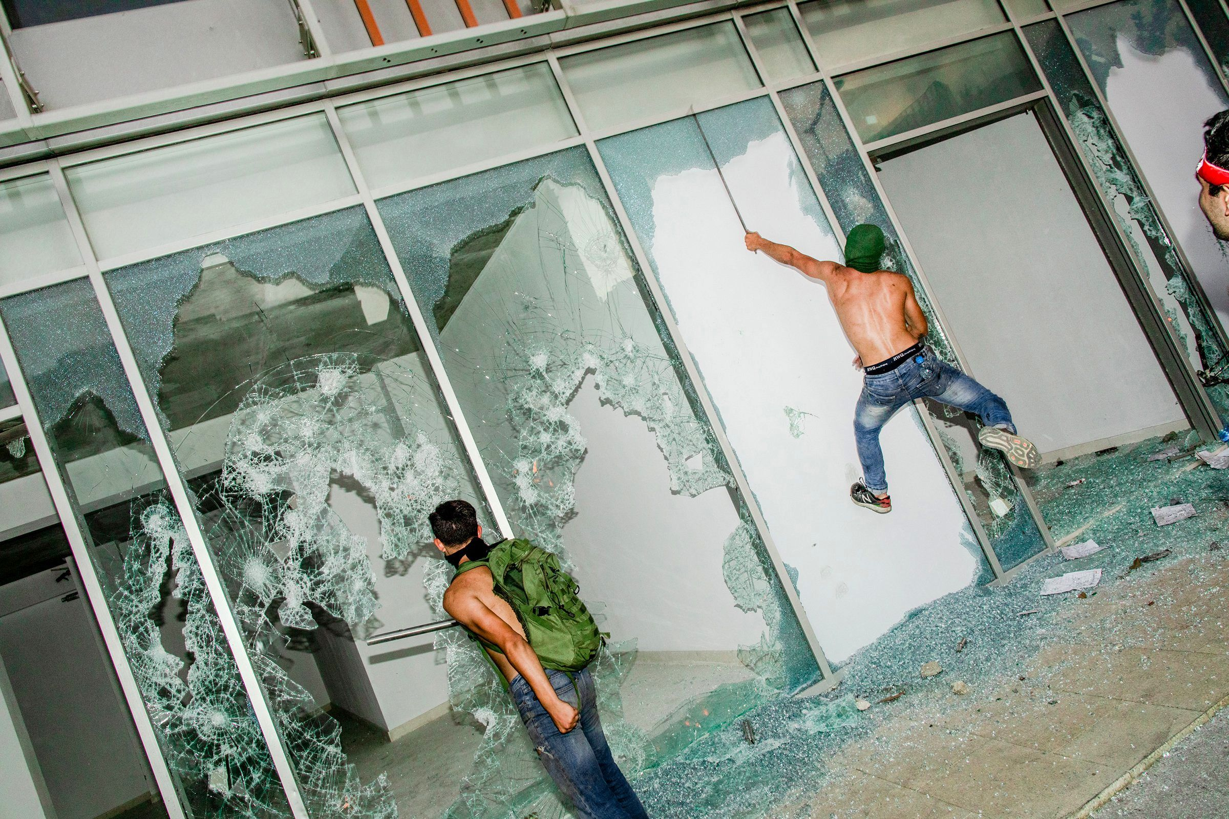 Young men smash shop windows on the first day of protests in Beirut on Oct. 18. After nearly two weeks of anti-government demonstrations aimed at dismantling the country's political system, Lebanese Prime Minister Saad Hariri resigned.