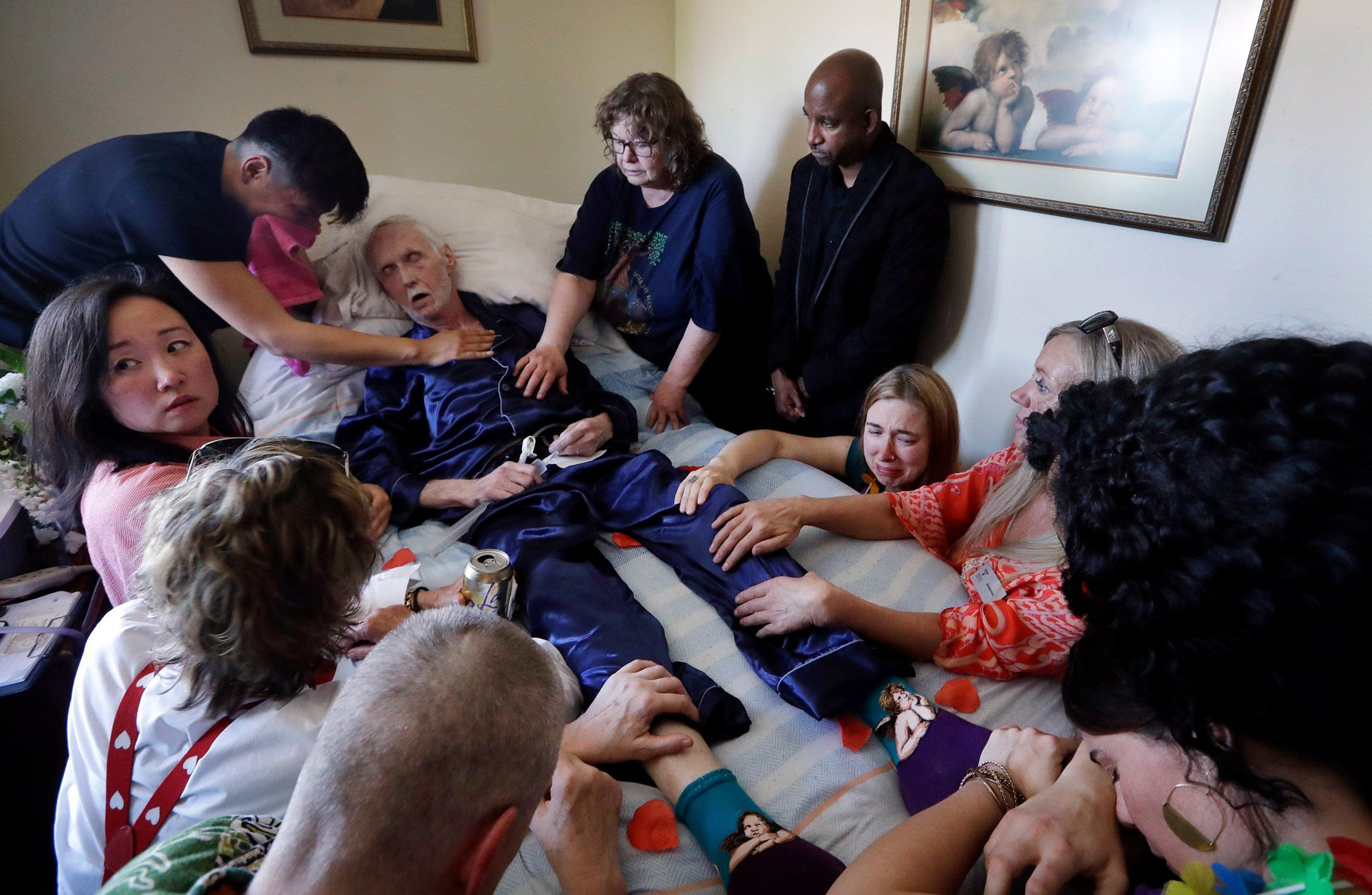 Robert Fuller lies unconscious after plunging prescribed drugs—to end his life—into his feeding tube in Seattle on May 10. Fuller's partner, Reese Baxter, top left, and friends lay their hands on him. The 75-year-old is one of about 1,200 people who have used Washington's Death with Dignity Act to end their lives in the decade since it became law.
