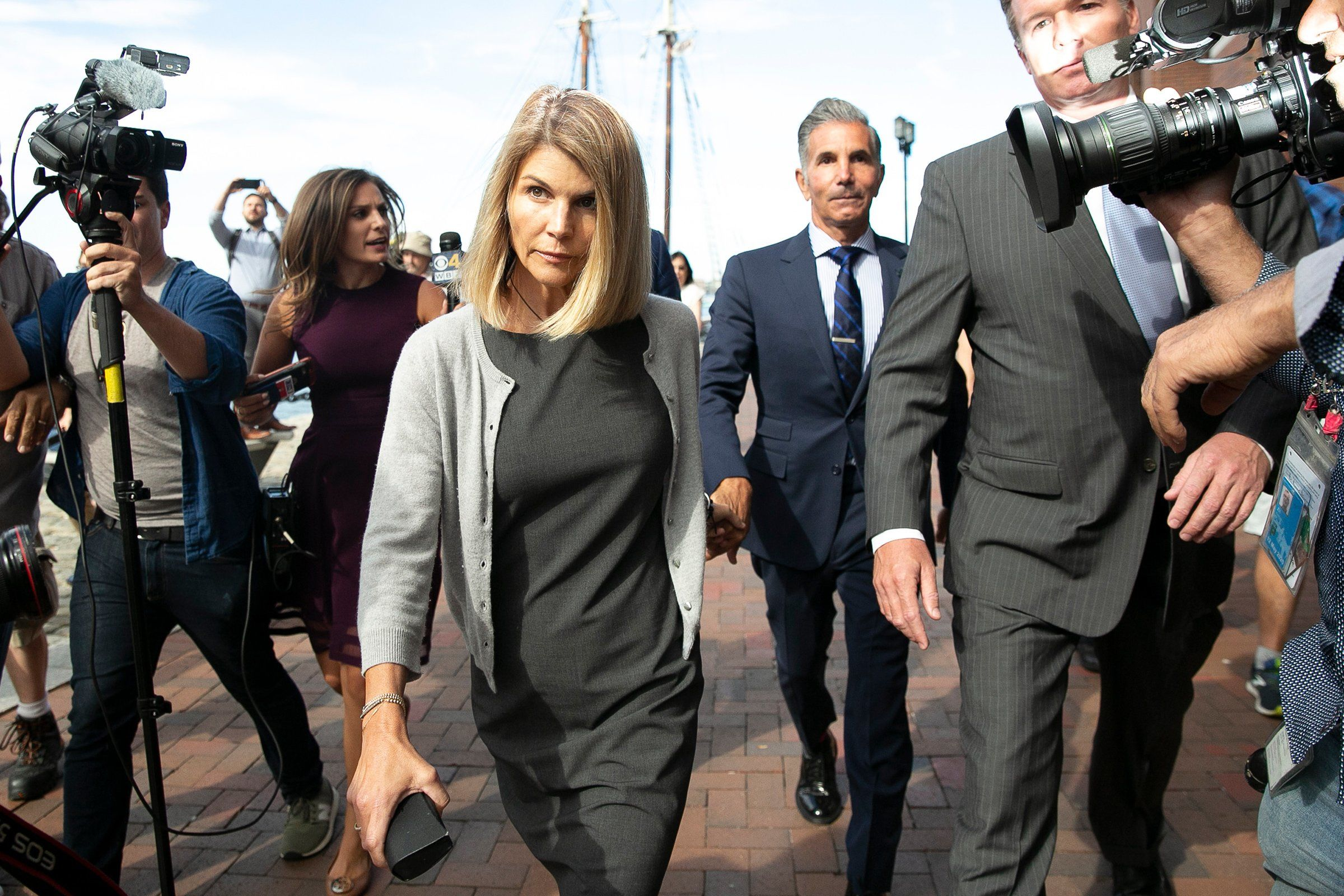"""Lori Loughlin and her husband, Mossimo Giannulli, leave federal court in Boston on Aug. 27. The """"Full House"""" actress and her fashion designer husband were charged with conspiring to pay bribes to get their daughters admitted to USC as recruits to the crew team."""